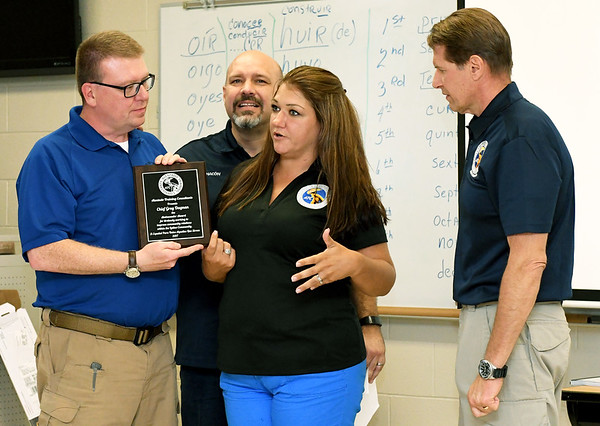 Carthage Police Chief Greg Dagnan, left,  receives a plaque from for his efforts of bringing the Spanish language class to Missouri Southern. Also pictured from the left: Alentado Training Consultants Lead Instructor Adam Chacon, Managing Director Andrea Alentado-Hague and Instructor Kevan Dugan. <br /> Globe | Laurie Sisk