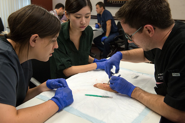 Globe/Roger Nomer<br /> Matt Brookes, a resident at Freeman Hospital, demonstrates a suture technique on a pig leg for Megan Schreier, left, a third-year student at AT Still University, and Winnie Hua, a third-year student at Kansas City University of Medicine and Biosciences Kansas City, on Friday at Freeman Hospital. The suture lab was for new core medical students at the hospital starting their clinical rotation.