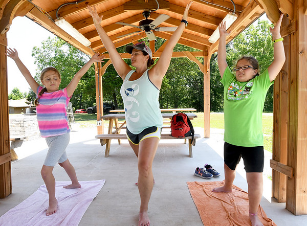 Sarah Brunner, center, of Fayetteville, teaches nine-year-old Addison Botzow, left and Emma McDowell, 10, the warrior pose as they learn a little about yoga on Thursday at Camp Mintahama.<br /> Globe | Laurie Sisk