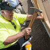 Globe/Roger Nomer<br /> Ron King hammers a wall on his new home on Wednesday with Habitat for Humanity.