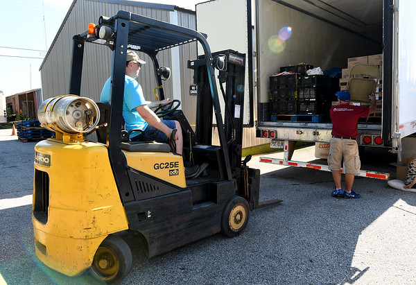 From the left: Volunteers Tim Edwards and Curtis Endicott transport food from a truck to the Feed the Heart food pantry on Thursday night in Carterville.<br /> Globe | Laurie Sisk