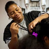 Globe/Roger Nomer<br /> Tanisha Reed works on Alexis McGill's hair at Reed's Barber Shop on Tuesday afternoon.