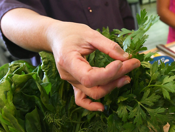 Josie MAi pulls a sprig of Italian flat parsley during a cooking class at Mai's Carthage home on Saturday.<br /> Globe | Laurie Sisk