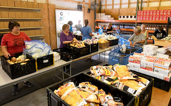Patrons begin to file in for a regular food distribution at the Carterville Christian Church's Feed the Heart food pantry on Thursday night.<br /> Globe | Laurie Sisk