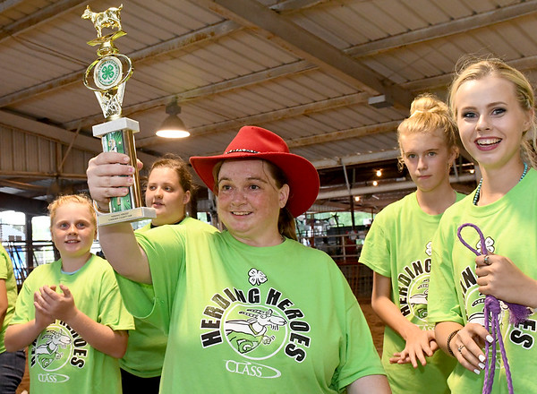 A proud Rebecca Miller, of Scammon, hoists her trophy as top shower during the Herding Heroes event at the Cherokee County Fair in Columbus, Kan. on Wednesday night. Also pictured, right, are her 4H partners Jadeyn Ivey, 12, of the Spring Valley Sparklers 4H Club and Savannah Meyer, 16, of the Lone Elm Beavers 4H Club.<br /> Globe | Laurie Sisk