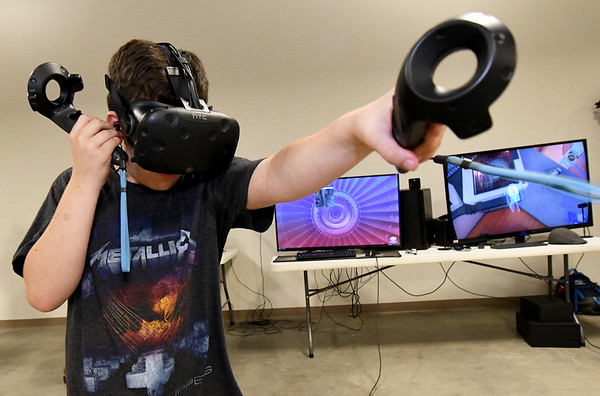 Fourteen-year-old Dustin Lehman checks out a portal-based virtual reality game on Saturday during the Joplin Makers Tool Drive at the Joplin Area Chamber of Commerce's Advanced Training and Technology Center. The event featured a 3D scanner, free food and characters in Star Wars attire.<br /> Globe | Laurie Sisk