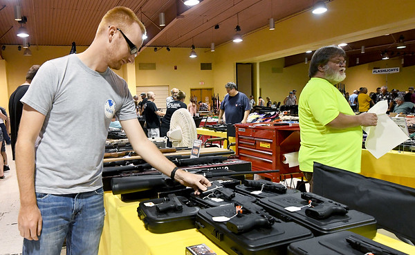 U.S. Army Sgt. Ethan Severance, formerly of Webb City, now serving at Fort Eustis, Va., checks out the selection of guns at the RK Gun Show on Saturday at the Joplin Convention Center. The show continues today from 9 am to 3 pm.<br /> Globe | Laurie Sisk
