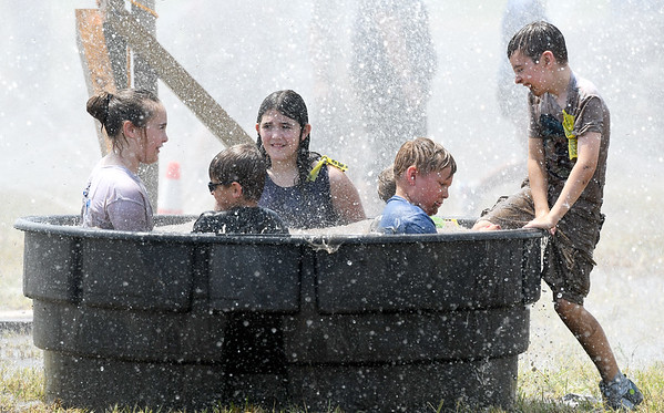 Youth rinse off in a stock tank after traversing a mud-filled course during Mudstock on Saturday in Carthage. The annual event is a drug awareness program sponsored by the Alliance of Southwest Missouri, with a course designed by Carthage Fire Department, Carthage Police Department, and the Carthage Caring Communities Coalition.<br /> Globe | Laurie Sisk