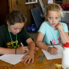 """From the left: Lola King, 11, Tatum Polozola, 9 and Karma Hensley, 10, take notes Thursday during a planning session for their """"Potter Party"""" - a Harry Potter-themed celebration to commemorate their last night at Camp Mintahama.<br /> Globe 