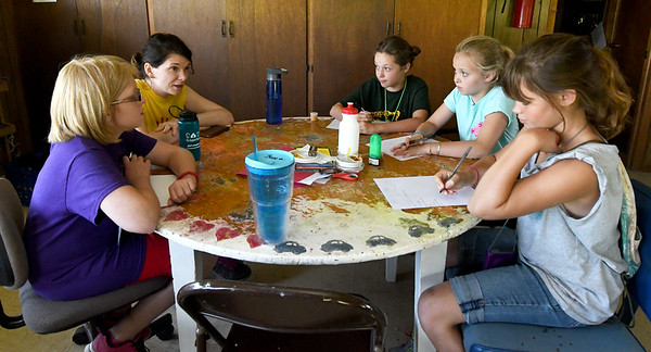 "From the left: Gwyneth Cleveland, 10, Counselor Holly Crane, Lola King, 11, Tatum Polozola, 9 and Karma Hensley, 10, chat Thursday during a planning session for their ""Potter Party"" - a Harry Potter-themed celebration to commemorate their last night at Camp Mintahama.<br /> Globe 