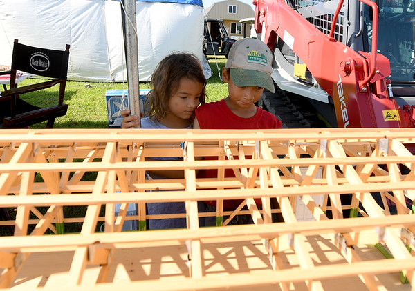 From the left: Six-year-old Rachel Roffmann and her nine-year-old brother, Peter Roffman, bth of Oronogo, check out a scale model of a pole barn at the Martin Metal and Yoder Designs exhibit during the first day of the Four States Farm Show on Friday in Pittsburg. The show continues through Sunday.<br /> Globe | Laurie Sisk