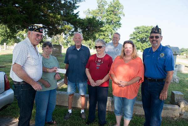 Globe/Roger Nomer <br /> (from left) CC Rock Conway, 15th district commander, Aurora, gives a check to Karen Brill, Carterville Cemetery Association president, with Dan Vangergrift, association members Shirley Reynolds, Tom Divine, Rhonda Rundle and Dan Musgrove, Post 91, Monett, present on Wednesday at the cemetery.