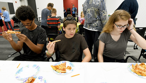from the left: Pizza connoisseurs Jermaine Loum, 13, Korbin Howard, 13 and Emily Doebele, 14, critique pizzas from five local pizzerias during the Joplin Public Library's Pizza Taste Test on Tuesday afternoon. Pizzas were judged in five categories: Crust, Cheese, Sauce, Aroma and Overall. Local businesses contributed about 30 pizzas for the 35 judges.<br /> Globe | Laurie Sisk