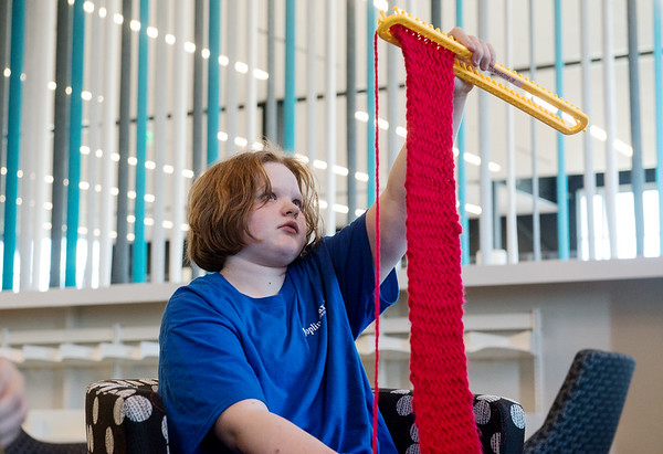 Globe/Roger Nomer<br /> Jackie Wiese, 12, checks the progress on her scarf while knitting on Monday at the Joplin Public Library.