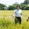Missouri Prairie Foundation Executive Director Carol Davit and MPF Director of Prairie Management Jerrod Huebner stand near assorted flowers last week on the Noah Brown Prairie. Dedication of the Prairie will be July 22.<br /> Globe | Laurie Sisk
