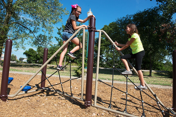 Globe/Roger Nomer<br /> Adaline Eldridge, 10, left, and Alexis Thompson, 9, climb on the spiderwebs on Monday at Ewert Park.
