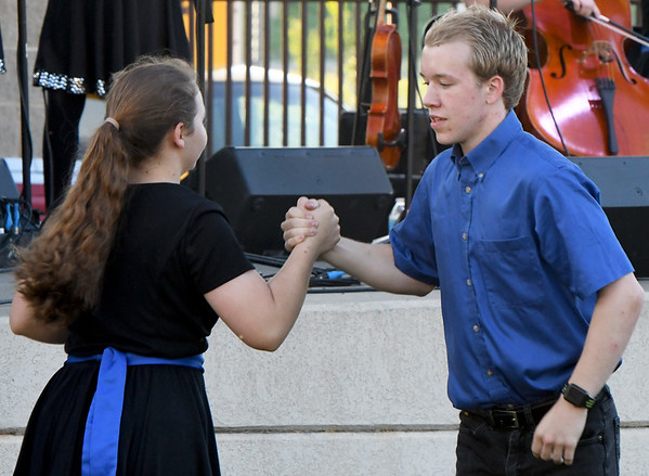 "Alison Vaujin, left, and Josh Mahaney , of the Saline Fiddlers Philharmonic show off their dancing skills during the ""Fiddlers on the Route"" music Festival on Saturday night at Landreth Park. The Connect2Culture event featured the Saline, Mi.-based group along with food and games for the children.<br /> Globe 