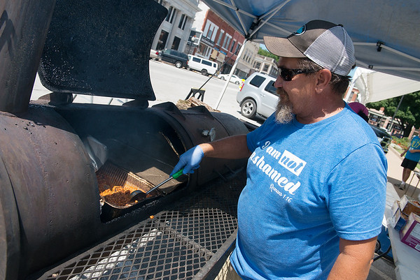Globe/Roger Nomer<br /> Tim Bowman, with Redneck Recipes, cooks on Thursday for the Carousel Kids Foundation fundraiser on the square in Neosho. The foundation was raising money to send foster children in Newton and McDonald County to summer camp.