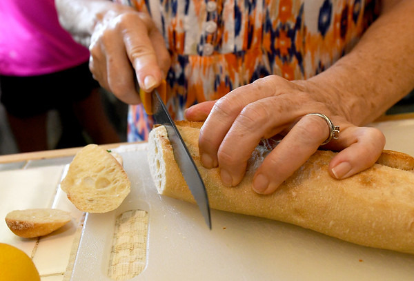 Brenda Spencer slices a bagette during a cooking class at Mai's Carthage home on Saturday.<br /> Globe | Laurie Sisk