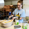 Camp Aide Carly Short, 17, dishes up sliced pears in preparation for dinner on Thursday at Camp Mintahama. Short is serving her second year as a camp aide and also attended the camp two years as a young girl.<br /> Globe | Laurie Sisk