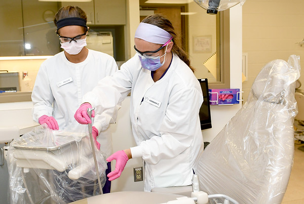 From the left: Missouri Southern dental hygiene students Felicia Wooten and Hannah Cook barrier wrap equipment on their last day of Summer Clinicals on Thursday at MSSU.<br /> Globe | Laurie Sisk