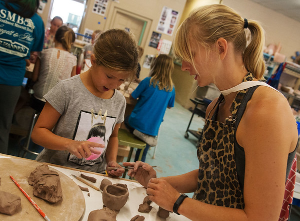 Globe/Roger Nomer<br /> Madison Wood, resident artist, helps Ella Jackson, 9, with a clay creation during the Summer Mud Clay Camp at Phoenix Fired Art on Monday.