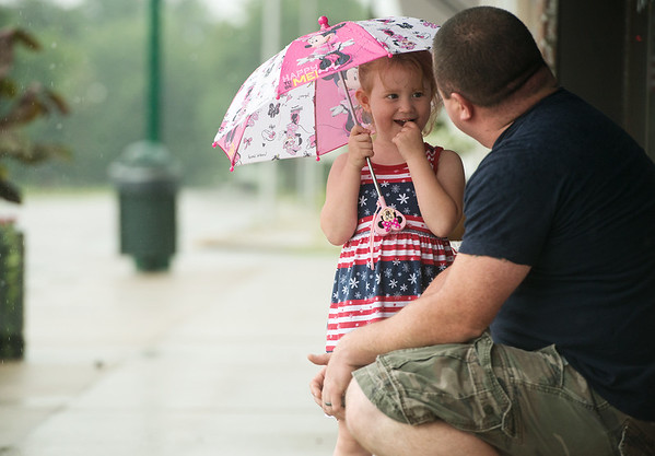 Globe/Roger Nomer<br /> Chloe, 4, and her father Colby Boyes, Carl Junction, take shelter as they wait out the rain before Tuesday's Carl Junction Fourth of July Parade.