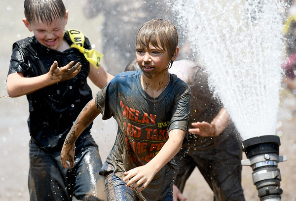 From the front: Zeppelin Bilinski, 8, of Wyandotte, John Mac, 10, of Carthage and Zackk Bilinski, 11, of Wyandotte, are all smiles as they traverse the course during Mudstock on Saturday in Carthage. The annual event is a drug awareness program sponsored by the Alliance of Southwest Missouri, with a course designed by Carthage Fire Department, Carthage Police Department, and the Carthage Caring Communities Coalition.<br /> Globe | Laurie Sisk
