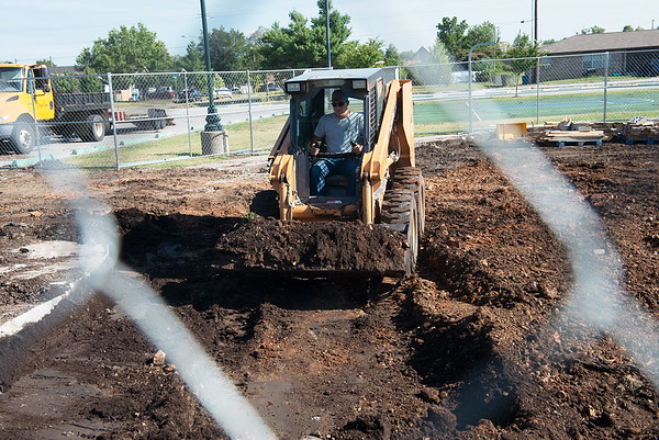 Globe/Roger Nomer<br /> Aaron Callis, with the city of Joplin, clears ground for new playground equipment on Monday at Parr Hill Park.