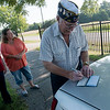 Globe/Roger Nomer<br /> CC Rock Conway, 15th district commander, Aurora, makes out a check to present to the Carterville Cemetery Association on Wednesday at the Carterville Cemetery.