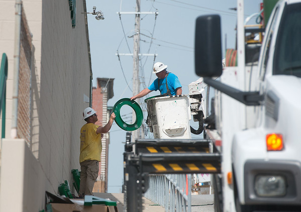 Globe/Roger Nomer<br /> Workers with Sign Designs install a sign for the Joplin Area Chamber of Commerce Advance Training and Technical Center on Wednesday.