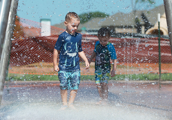 Globe/Roger Nomer<br /> Brothers Kaleb, 4, and Chance, 3, Tucker cool off in the splash pad at King Jack Park on Monday.