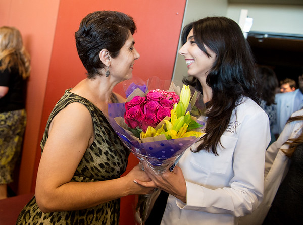 Globe/Roger Nomer<br /> Gayane Mirzoyan, Armenia, greets her daughter Aspram Sargsyan with flowers following Monday's Kansas City University of Medicine and Biosciences White Coating Ceremony at Joplin High School.