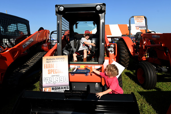 Five-year-old Chester Phillips and his three-year-old sister Iscel Phillips, both of Cherryvale, check out the Kubota equipment at Romans Outdoor Power display during the first day of the Four States Farm Show on Friday in Pittsburg.<br /> Globe | Laurie Sisk