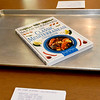 A cookbook rests center-table as participants await the preparation of a Mediterranean meal during a cooking class at Josie Mai's Carthage home.<br /> Globe | Laurie Sisk
