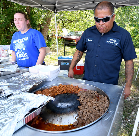 Ghetto Taco owner Marcos Renteria and his daughter, Ashley Linder watch over asada, pastor and chicken at their pop up food stand on East 7th street on Tuesday.<br /> Globe | Laurie Sisk