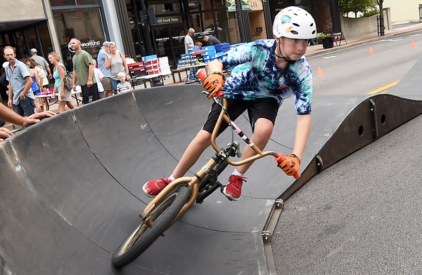 Twelve-year-old Blane Dumas, of Seneca, checks out the ramp supplied by Progressive Bike Ramps as shoppers peruse the sidewalk sale bargains during Bike Downtown on Saturday in Downtown Joplin. The event featured games, food, bike races and more and was sponsored by the Joplin Area Chamber of Commerce Young Professionals, JOMO Adventures and the Downtown Joplin Alliance.<br /> Globe | Laurie Sisk