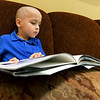 Six-year-old Micah Schisler, of Webb City - part of a family of volunteers at the Ronald McDonald House of the Four States - enjoys a book during the 20th Birthday celebration for RMH on Friday. With many of the volunteers spending numerous hours at the house, Schisler seemed at home during the celebration.<br /> Globe | Laurie Sisk