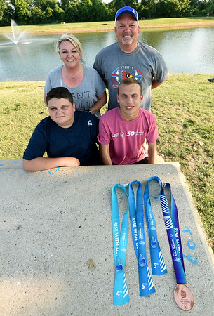 Eighteen-year-old distance runner and Special Olympian Brett Harper, lower right, poses with his family on Wednesday at King Jack Park. Pictured are Harper's brother, William Harper, 13, his mother, Sheila Harper and father, Bill Harper.<br /> Globe   Laurie SIsk