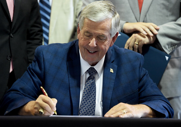 Missouri Gov. Mike Parson signs Missouri House Bill 2540 on Thursday at Hartman & Co. in Springfield. The plan lowers Missouri's personal income tax rate from 5.9 percent to 5.5 percent effective Jan. 1. and allows personal income tax rates to to dip to 5.1 percent if the state hits revenue targets in the future.<br /> Globe   Laurie Sisk