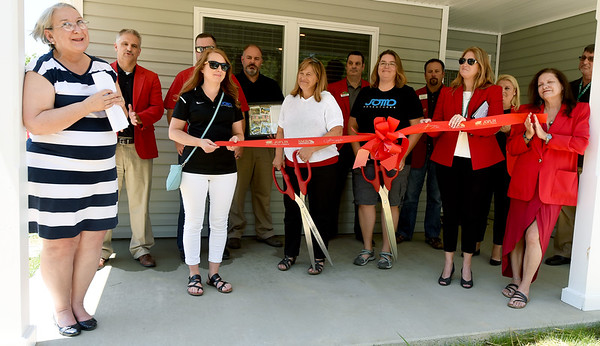 Lafayette House Executive Director Alison Malinowski Sunday, left, thanks those who helped make new transitional housing for clients a reality during a ribbon cutting ceremony for the house on Friday. Joining Malinowski Sunday are representatives of JOMO Adventures, both Carl Junction and Joplin Area Chambers of Commerce and others who donated to the house.<br /> Globe   Laurie Sisk