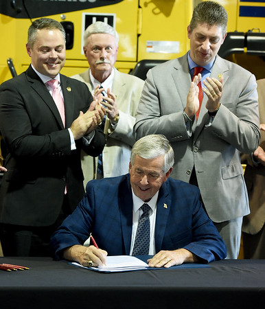 Missouri Gov. Mike Parson signs Missouri's House Bill 2540 into law on Thursday at Hartman & Co. in Springfield as Speaker Pro Tem Ejijah Haahr and Sen. Bill Eigel look on. Haahr and Eigel were both instrumental in shepherding the bill through the state legislature. The plan lowers Missouri's personal income tax rate from 5.9 percent to 5.5 percent effective Jan. 1. and allows personal income tax rates to to dip to 5.1 percent if the state hits revenue targets in the future.<br /> Globe | Laurie Sisk
