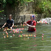 Seneca kids help the ducks along in calm water during the duck race at Seneca's Little Town, Big Boom celebration on Saturday in downtown Seneca. The event served as both the town's 150th birthday and an Independence Day celebration, featuring a parade, games, food and more.<br /> Globe | Laurie Sisk