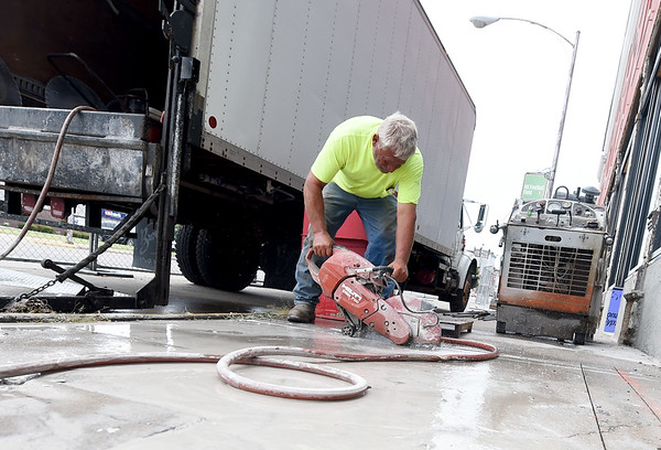 Rodney Garringer, of Sproul's Construction, Inc., prepares a side walk for installation of a handicap ramp as construction continues on the Block 22 project on Thursday in downtown Pittsburg.<br /> Globe   Laurie Sisk