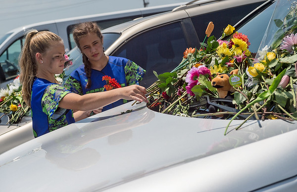 Kamryn Collier, 14, left, and Erin McMaster, 13, from Hope, Ark., place flowers on a car at the Ride the Ducks attraction in Branson on Friday.<br /> Globe   Roger Nomer