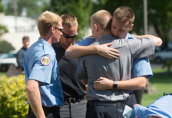 J. Ryan Wood, right, comforts his fellow Western Taney County first responders embrace following Sunday's memorial service at the College of the Ozarks. Many of the first responders attending worked the boat accident on Table Rock Lake on Thursday.<br /> Globe   Roger Nomer