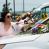 Bailey Eutsler, Crane, leaves flowers on windshields of abandoned cars at the Ride the Ducks attraction in Branson on Friday.<br /> Globe | Roger Nomer