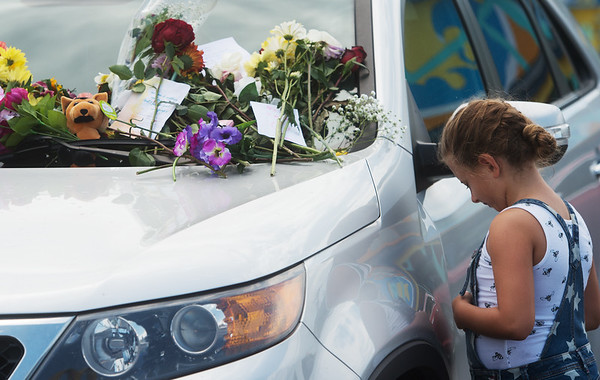 Saylor Lembke, 8, Kansas City, Mo., bows her head for prayer by an abandoned car at the Ride the Ducks attraction on Friday in Branson.<br /> Globe   Roger Nomer