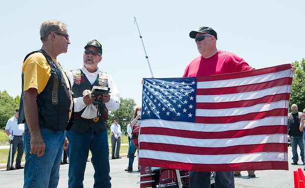 Ryan Mitchell, right, and Chuck Vrana, center, from American Legion Post 136 in Mulvane, Kan., transfer an American flag to Steve Lea, Joplin, during the annual Nation of Patriots tour during a stop on Saturday at Hideout Harley Davidson. The Nation of Patriots tour escorts a flag, carried by motorcyclists, across 48 states to honor American military.<br /> Globe | Roger Nomer