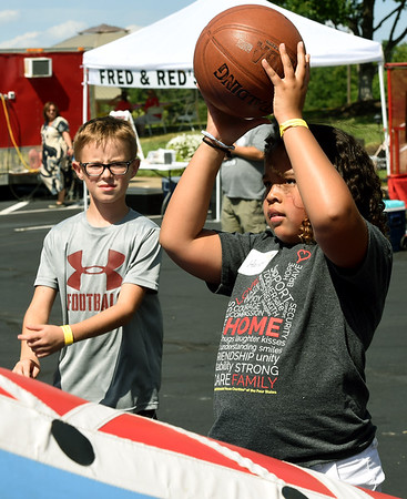 Nine-year-old Harper Mathis, right, checks out an inflatable game with her friend, Jamohn Smith, 10, during the Ronald McDonald of the Four States 20th Birthday celebration on Friday at RMH. Harper is the third generation of her family to volunteer at RMH since its opening 20 years ago.<br /> Globe | Laurie Sisk